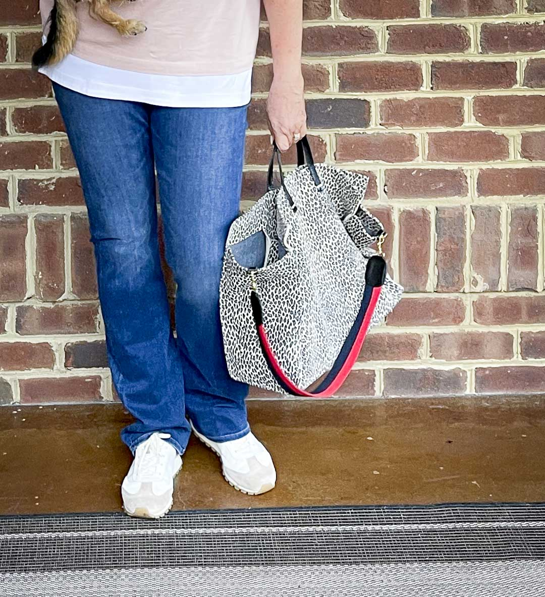 Over 40 Fashion Blogger, Tania Stephens, is wearing bootcut jeans and carrying a suede animal print tote