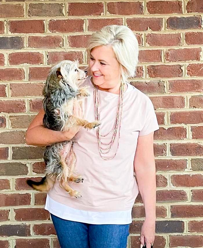 Over 40 Fashion Blogger, Tania Stephens, is dressed in blush pink, a white tank tunic and holding her dog
