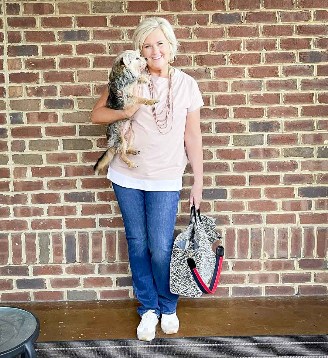 Over 40 Fashion Blogger, Tania Stephens, is holding her dog while dressed in blush pink, a white tank tunic, bootcut jeans, and carrying a suede animal print tote