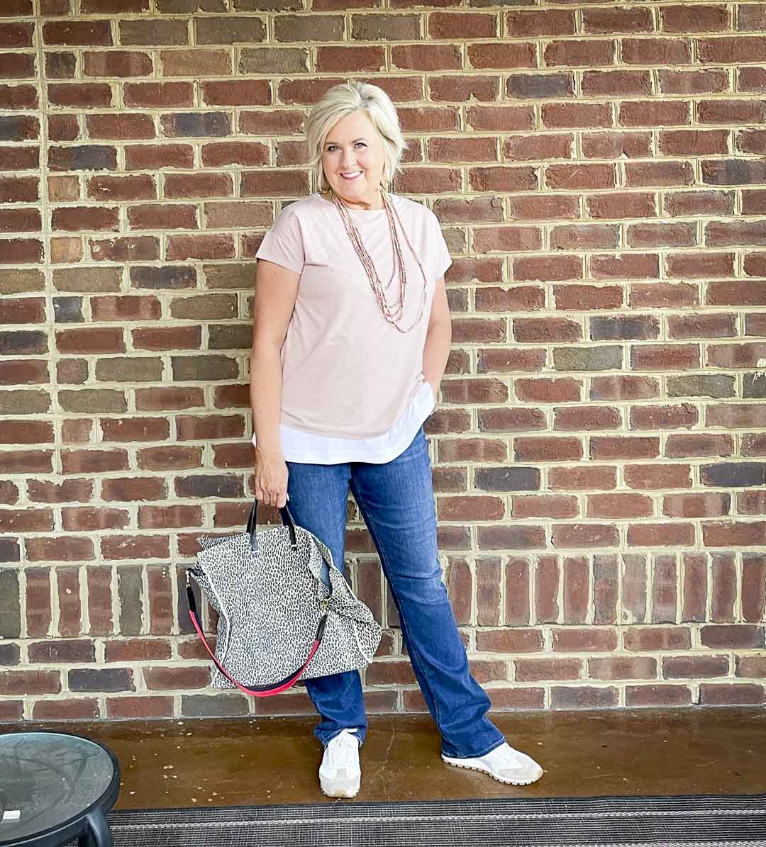 Over 40 Fashion Blogger, Tania Stephens, is wearing a blush pink, a white tank tunic, bootcut jeans, and carrying a suede animal print tote