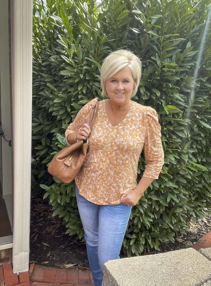 Over 40 Fashion Blogger, Tania Stephens, is wearing one of her puff sleeve tops with a light blue pair of jeans