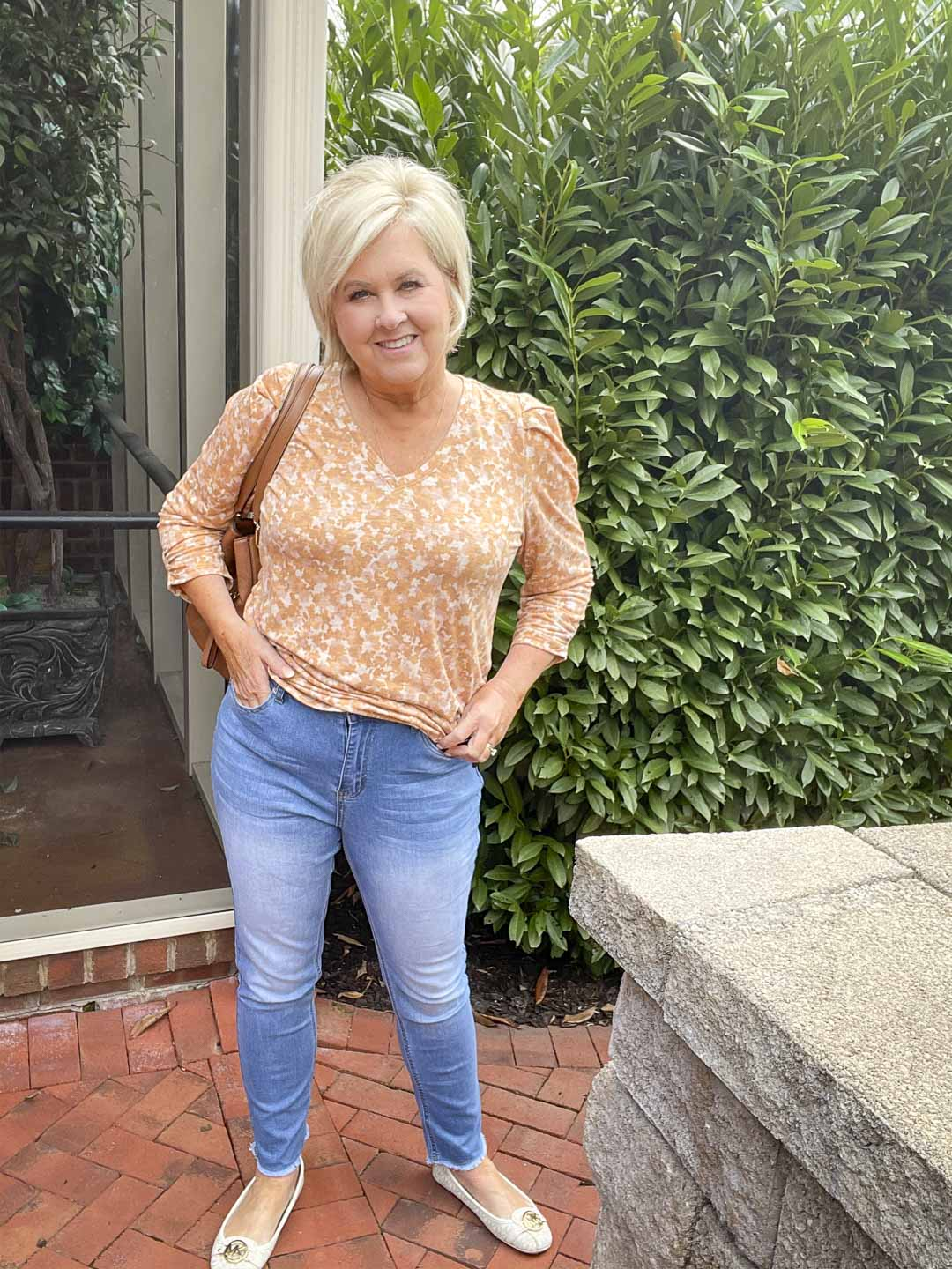 Over 40 Fashion Blogger, Tania Stephens, is wearing one of her puff sleeve tops with a light pair of jeans and monogrammed loafers