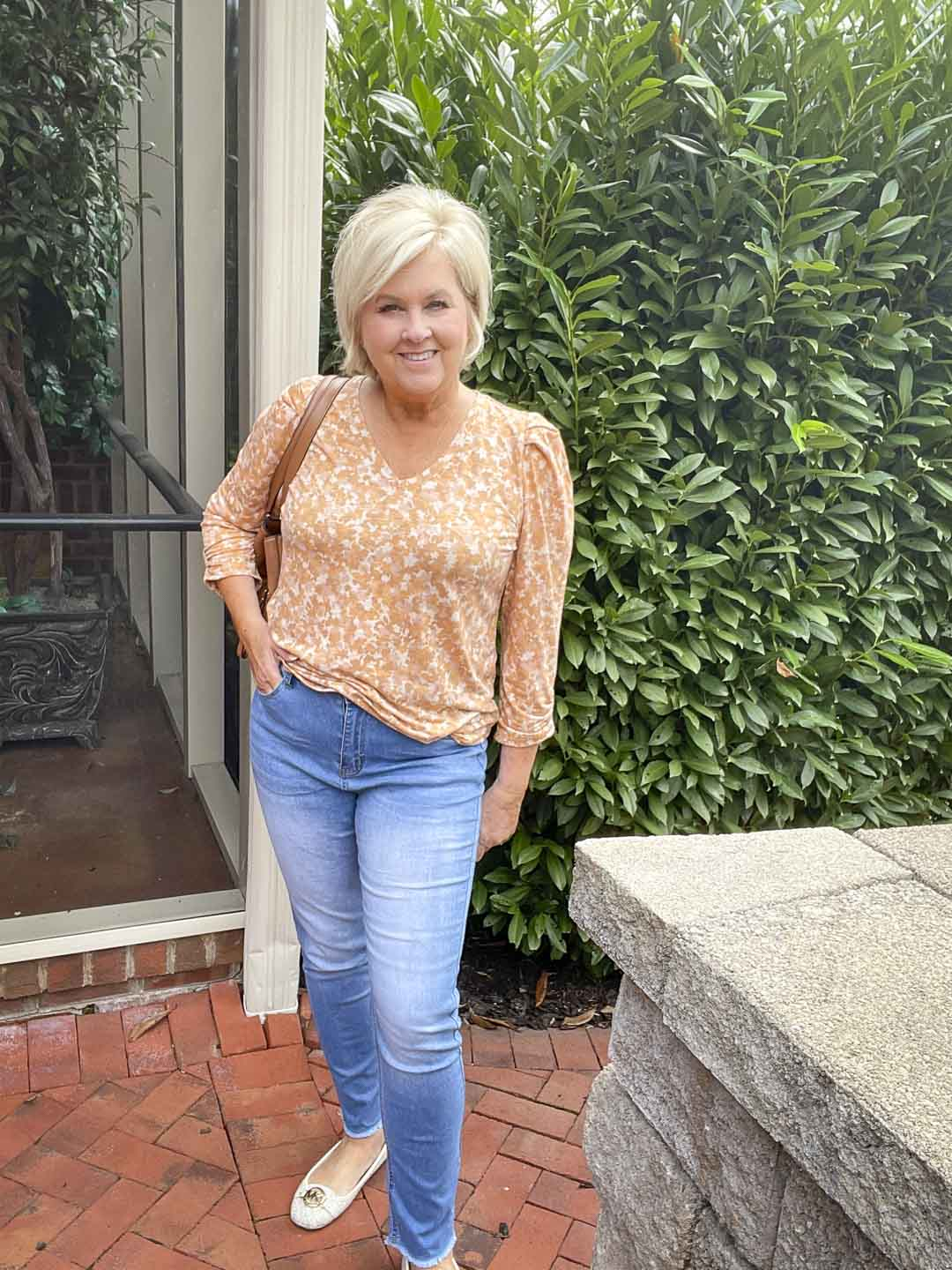 Over 40 Fashion Blogger, Tania Stephens, is wearing one of her puff sleeve tops with a light blue pair of jeans and monogrammed loafers