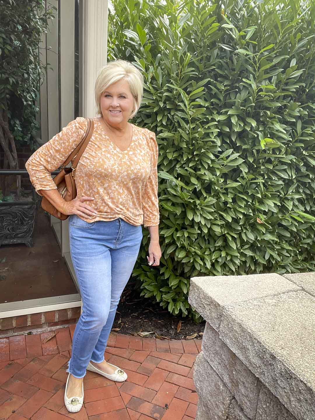 Over 40 Fashion Blogger, Tania Stephens, is wearing one of her puff sleeve tops with a light blue pair of jeans and monogrammed loafers from Michael Kors