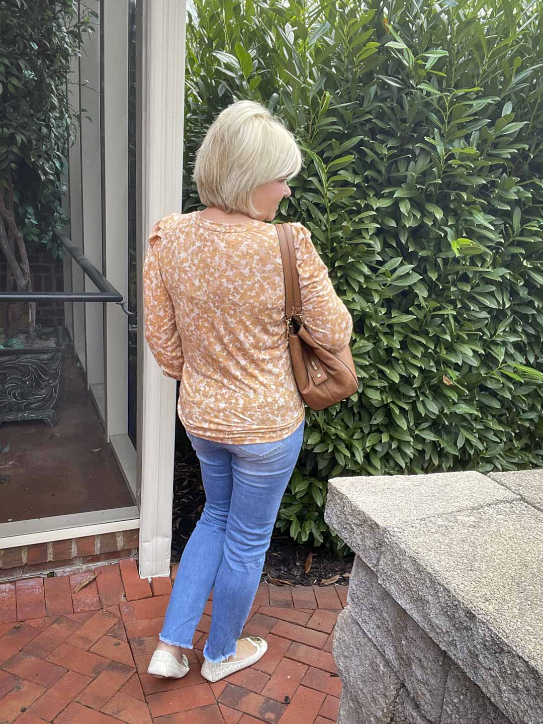 Over 40 Fashion Blogger, Tania Stephens, is showing the back of one of her puff sleeve tops with a light blue pair of jeans and monogrammed loafers from Michael Kors