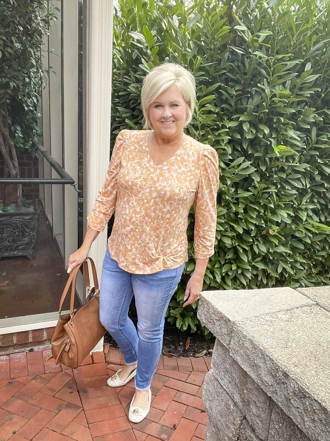 Over 40 Fashion Blogger, Tania Stephens, is wearing one of her puff sleeve tops with a light blue pair of jeans and carrying a brown handbag