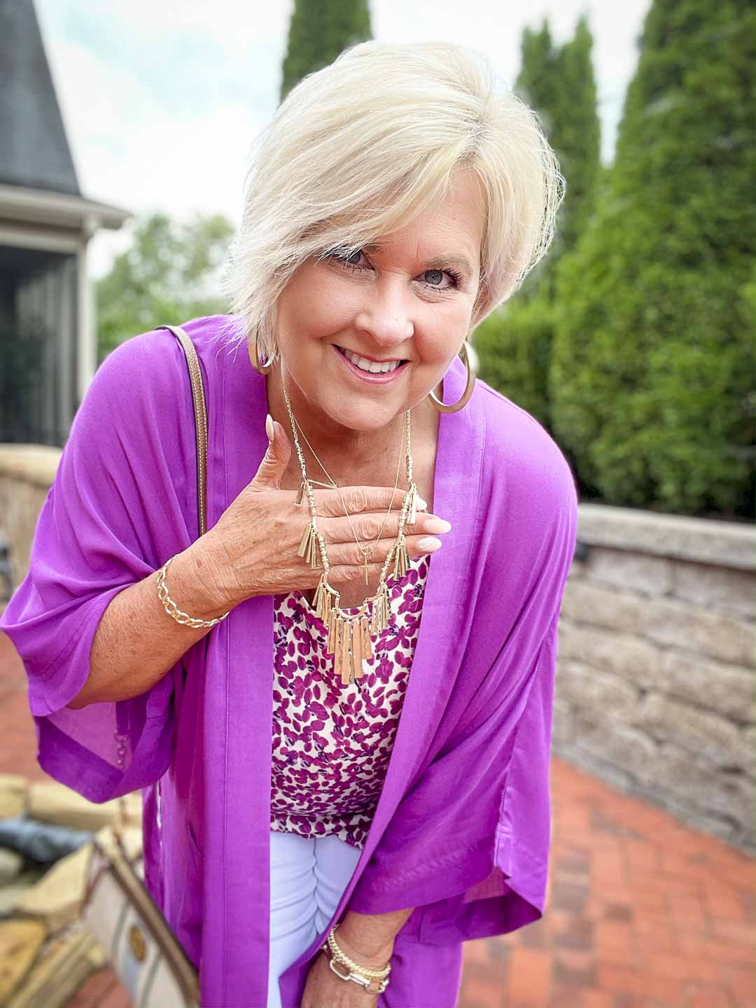 Over 40 fashion blogger, Tania Stephens is wearing a purple cardigan with gold jewelry