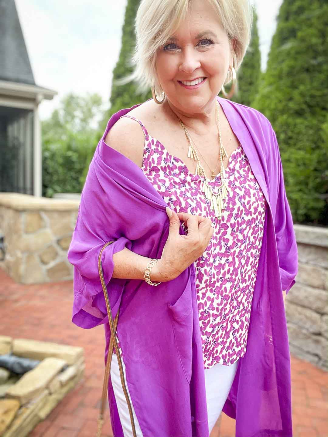 Over 40 fashion blogger, Tania Stephens is wearing a purple cardigan with a printed camisole with gold jewelry