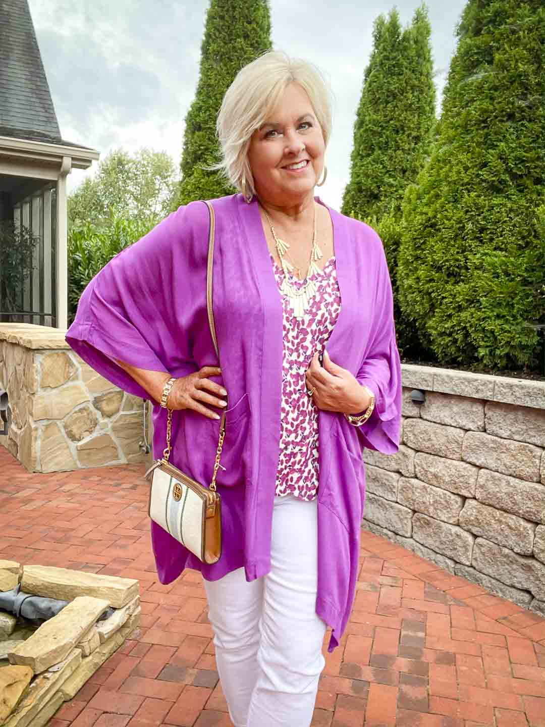 Over 40 fashion blogger, Tania Stephens is wearing a purple cardigan with white jeans