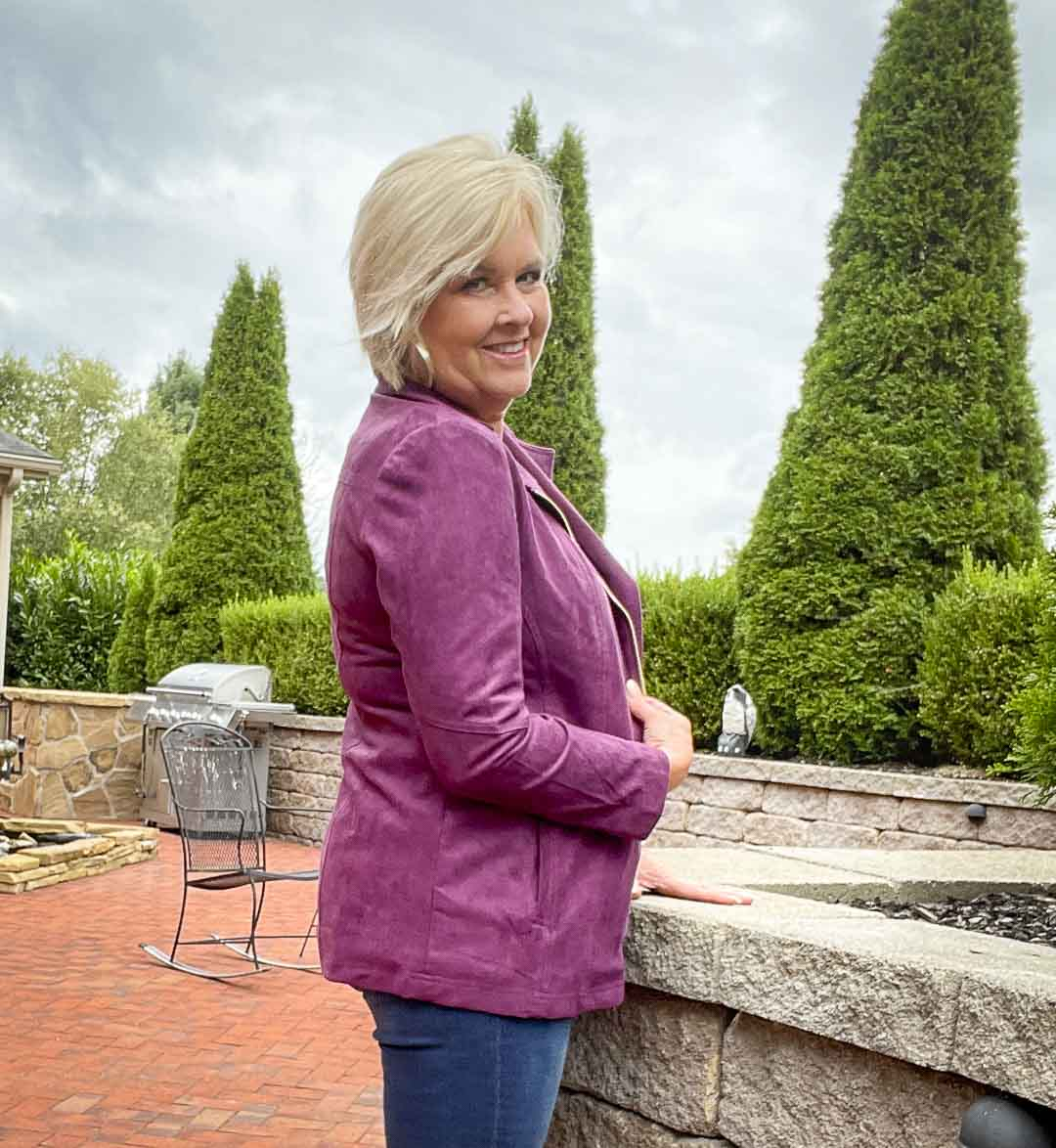 Over 40 fashion blogger, Tania Stephens is showing the side of a plum moto jacket from Chico's