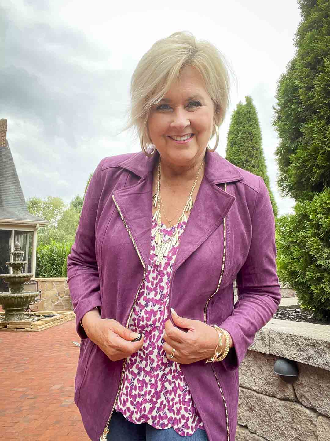 Over 40 fashion blogger, Tania Stephens is wearing a plum moto jacket with a printed camisole