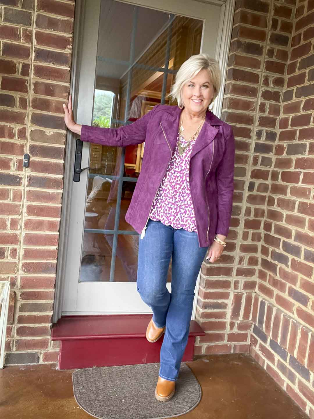 Over 40 fashion blogger, Tania Stephens is wearing a plum moto jacket, a camisole, bootcut jeans, and lug boots