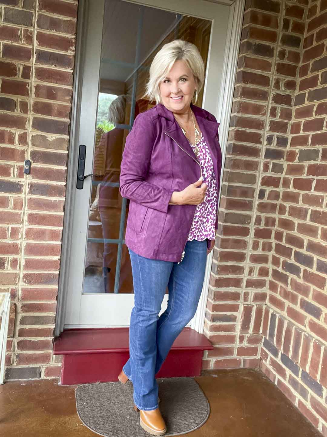 Over 40 fashion blogger, Tania Stephens is wearing a plum moto jacket, a printed camisole, bootcut jeans, and lug boots