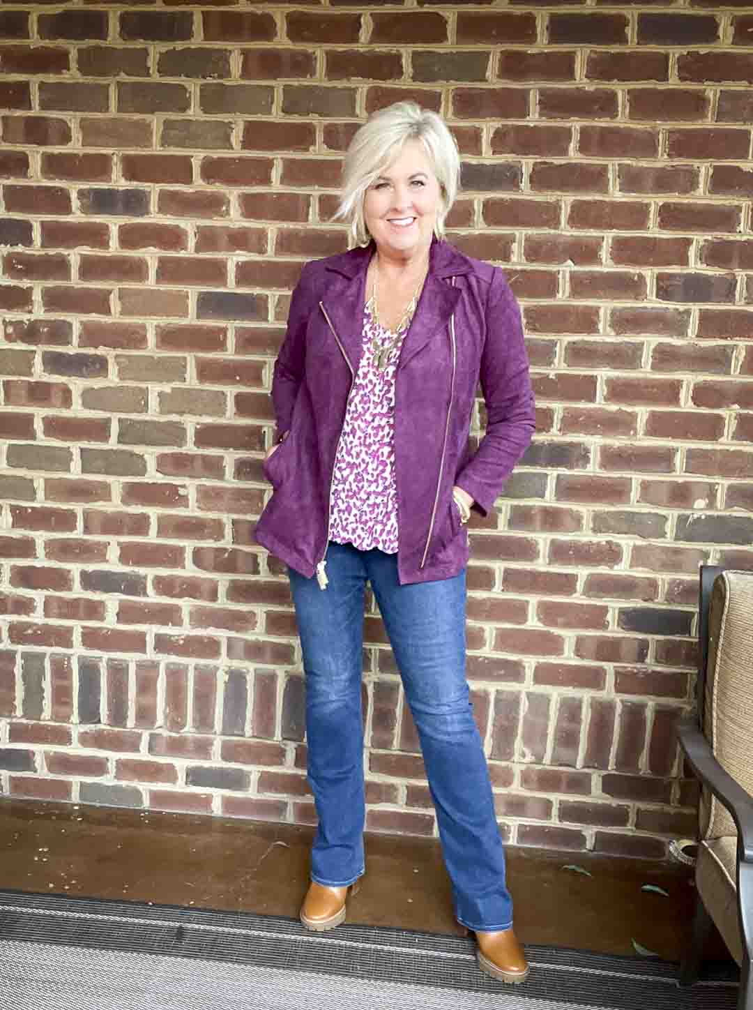 Over 40 fashion blogger, Tania Stephens is wearing a plum moto jacket, a printed camisole, bootcut jeans, and Tory Burch lug boots