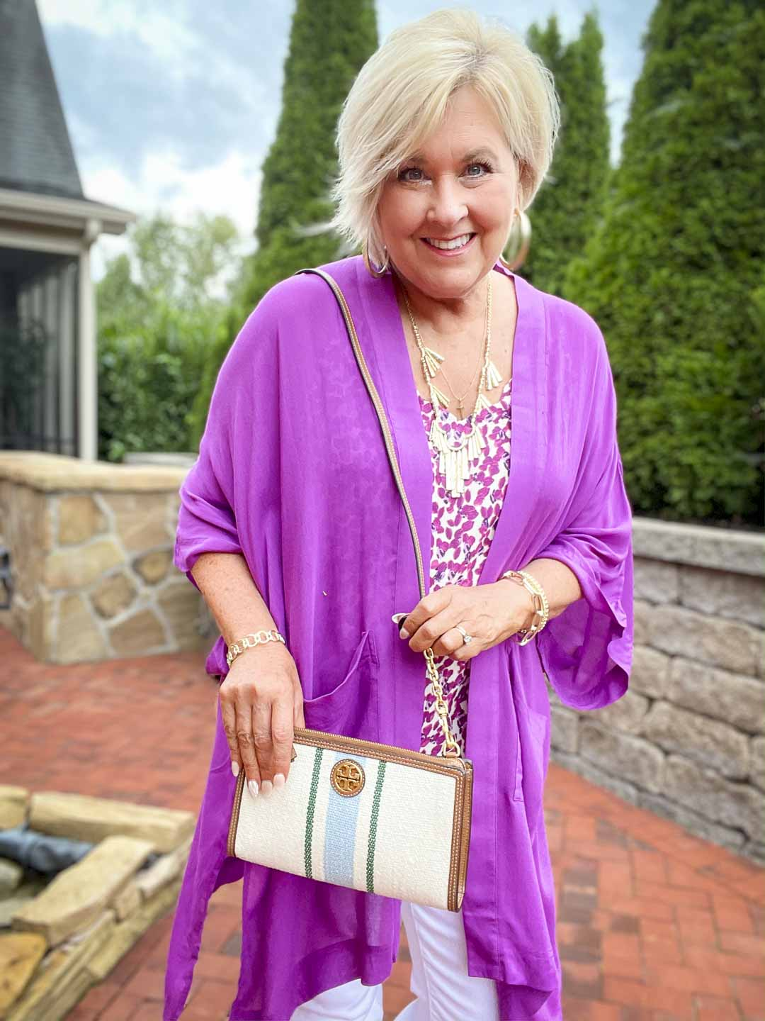 Over 40 fashion blogger, Tania Stephens is wearing a purple cardigan with a printed camisole and holding a Tory Burch crossbody