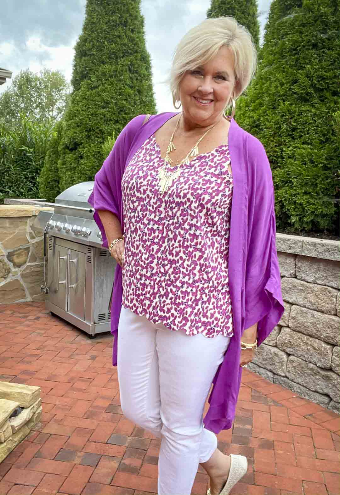 Over 40 fashion blogger, Tania Stephens is wearing a purple cardigan, white jeans, a printed camisole, and gold jewelry