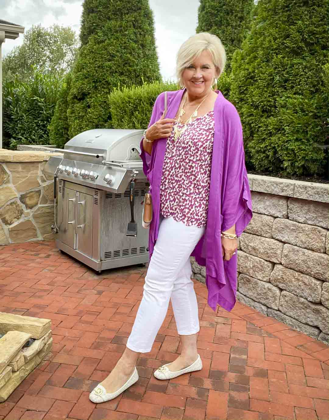 Over 40 fashion blogger, Tania Stephens is wearing a purple duster, a printed camisole, white jeans, and white flats
