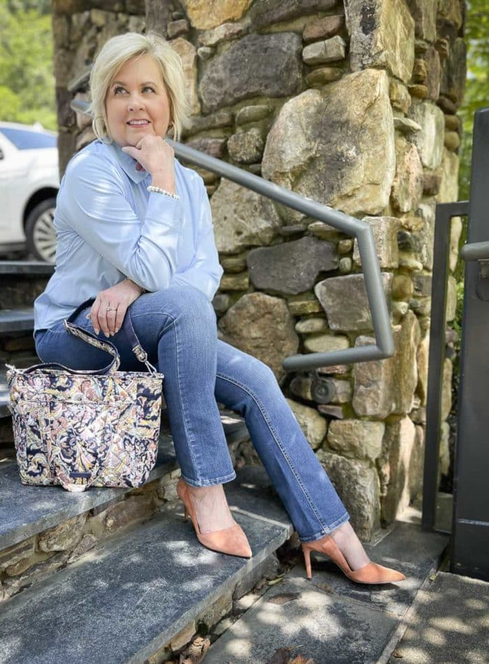 Over 40 Fashion Blogger, Tania Stephens is sitting on steps wearing a button shirt, jeans, and clay colored heels