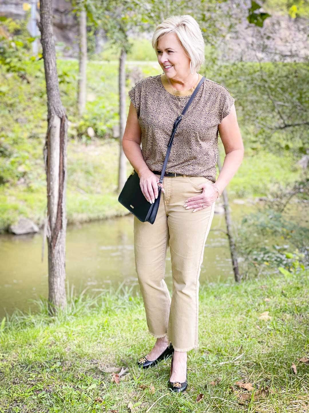Over 40 Fashion Blogger, Tania Stephens is wearing animal print for fall, tan cropped jeans, and a black crossbody handbag