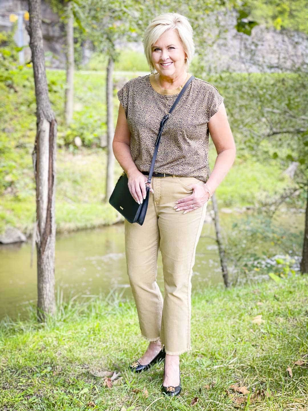 Over 40 Fashion Blogger, Tania Stephens is wearing animal print for fall, cropped jeans, and a black crossbody handbag