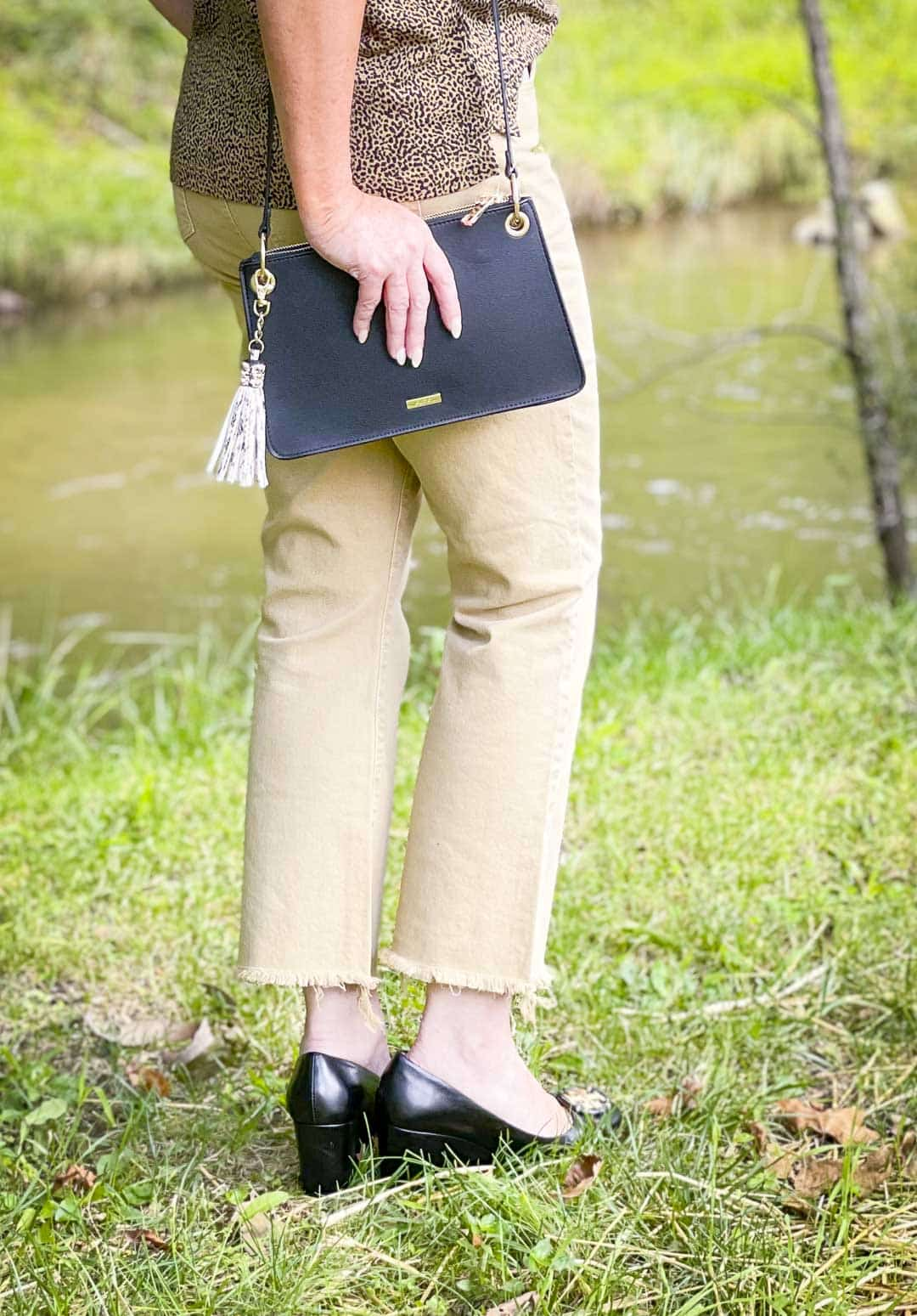 Over 40 Fashion Blogger, Tania Stephens is wearing tan cropped jeans and carrying a black handbag