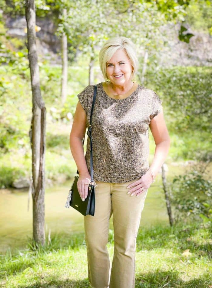 Over 40 Fashion Blogger, Tania Stephens is wearing animal print, tan cropped jeans, and carrying a black handbag for fall
