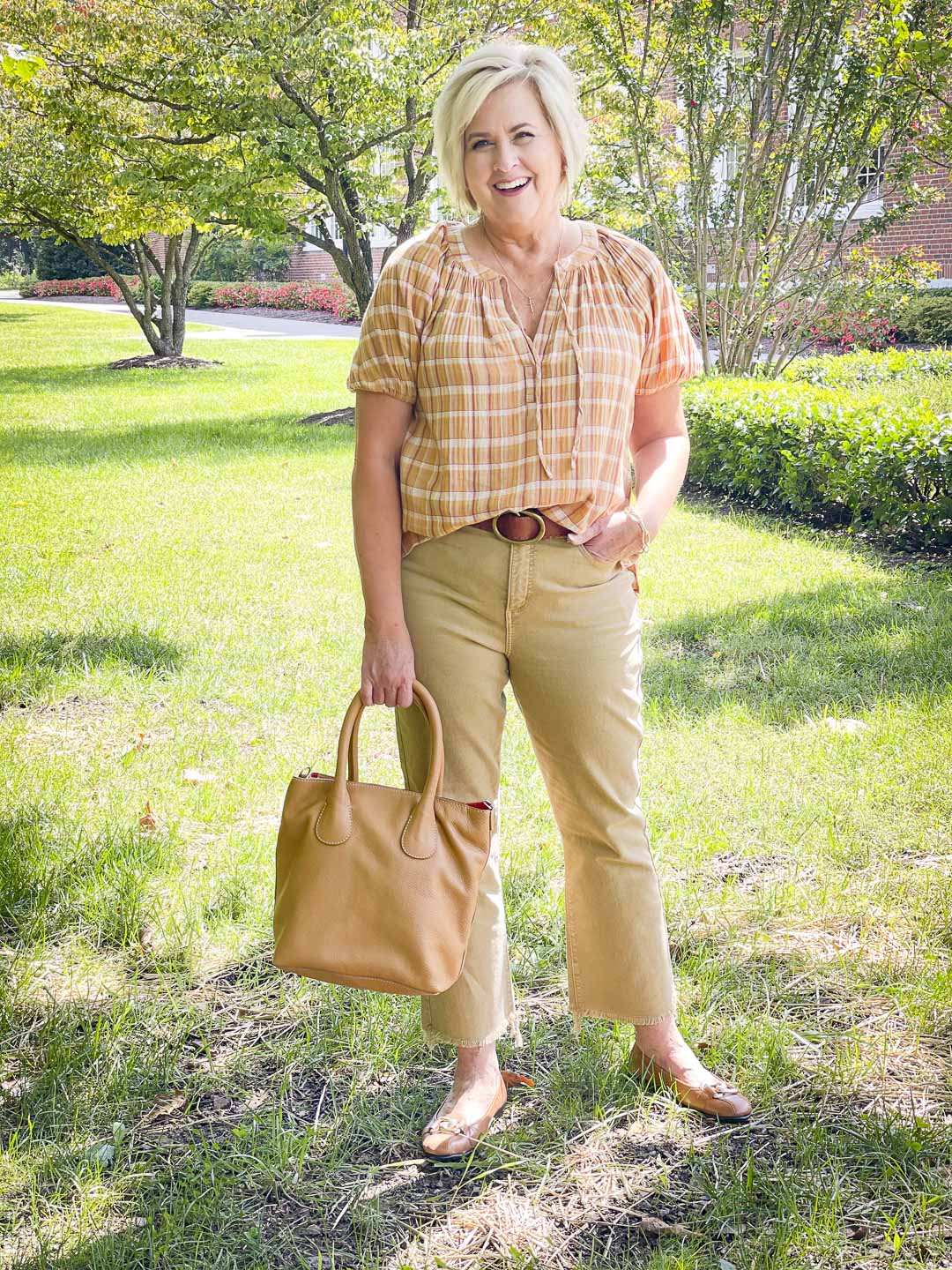 Over 40 Fashion Blogger, Tania Stephens, looks casual in her fall festive plaid top, cropped jeans, and camel handbag