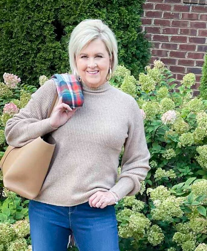 Over 40 Fashion Blogger, Tania Stephens, is wearing a ribbed mock neck sweater
