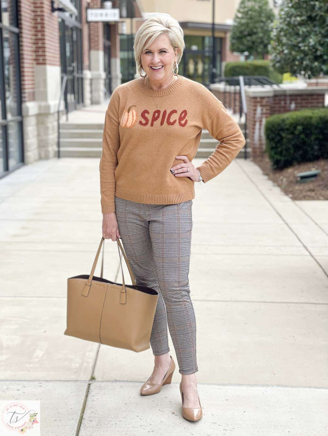 Over 40 Fashion Blogger, Tania Stephens, is wearing a Pumpkin Spice sweater, a pair plaid Ponte knit pants, and taupe wedges