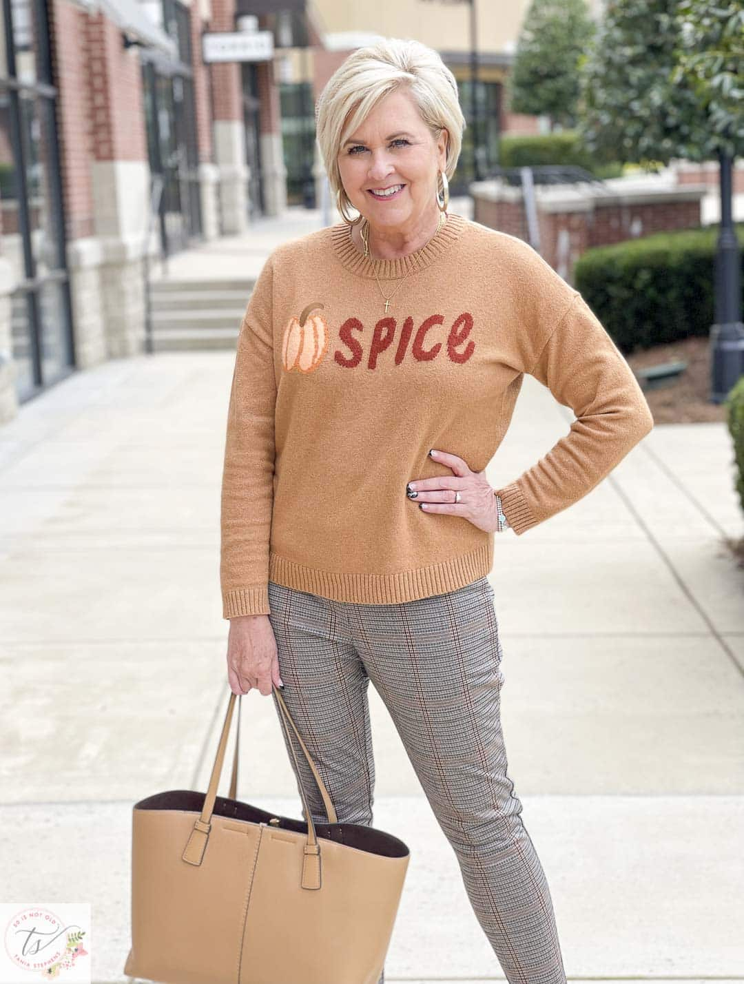 Over 40 Fashion Blogger, Tania Stephens, is wearing a Pumpkin Spice sweater, a pair plaid Ponte knit pants, a Tory Burch handbag, and taupe wedges