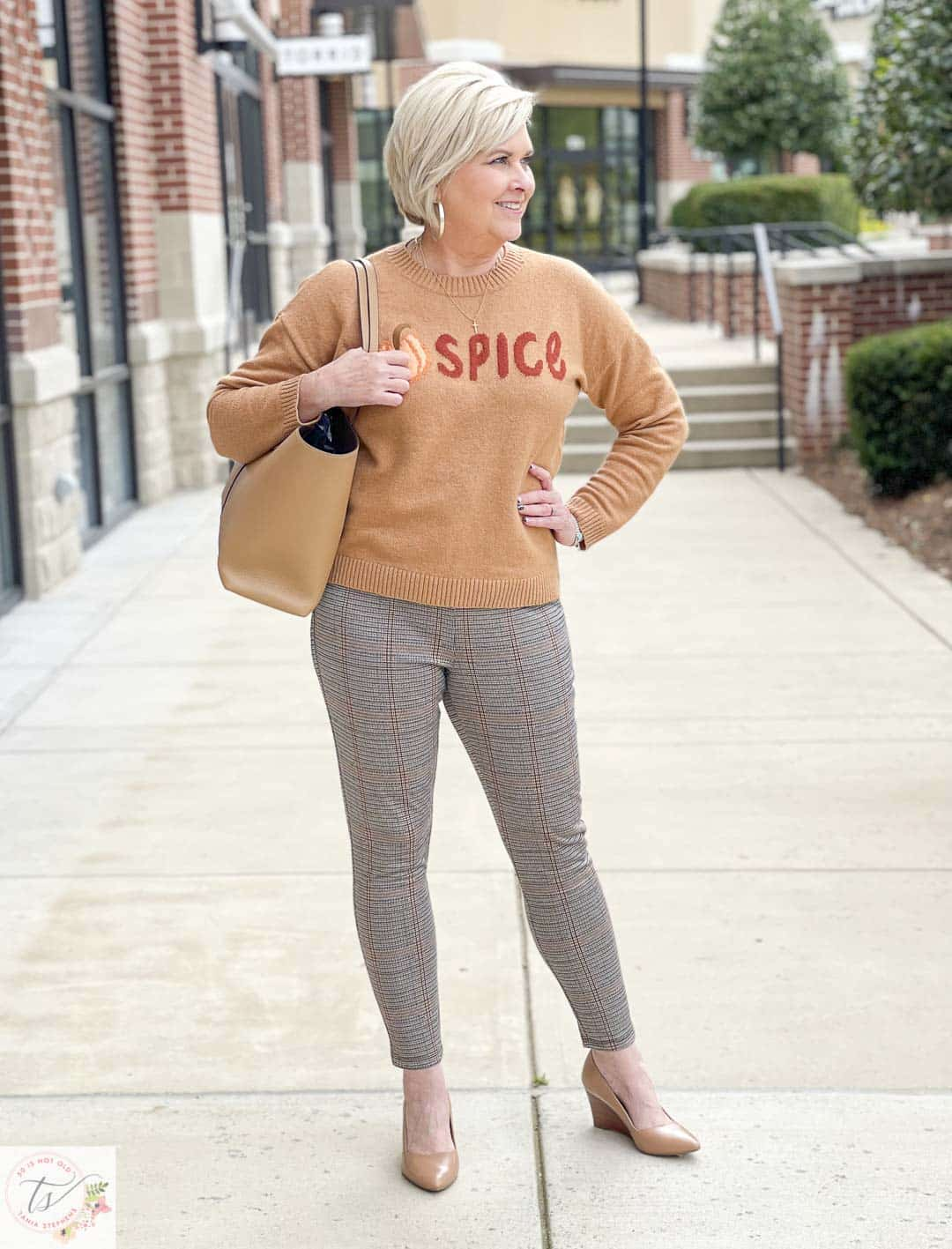 Over 40 Fashion Blogger, Tania Stephens, is wearing a Pumpkin Spice sweater with a pair of taupe wedges, and plaid Ponte knit pants