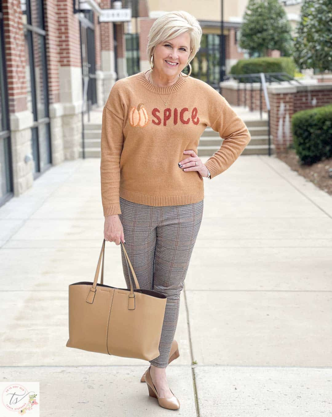 Over 40 Fashion Blogger, Tania Stephens, is wearing a Pumpkin Spice sweater with a pair of taupe wedges, a Tory Burch handbag, and plaid Ponte knit pants