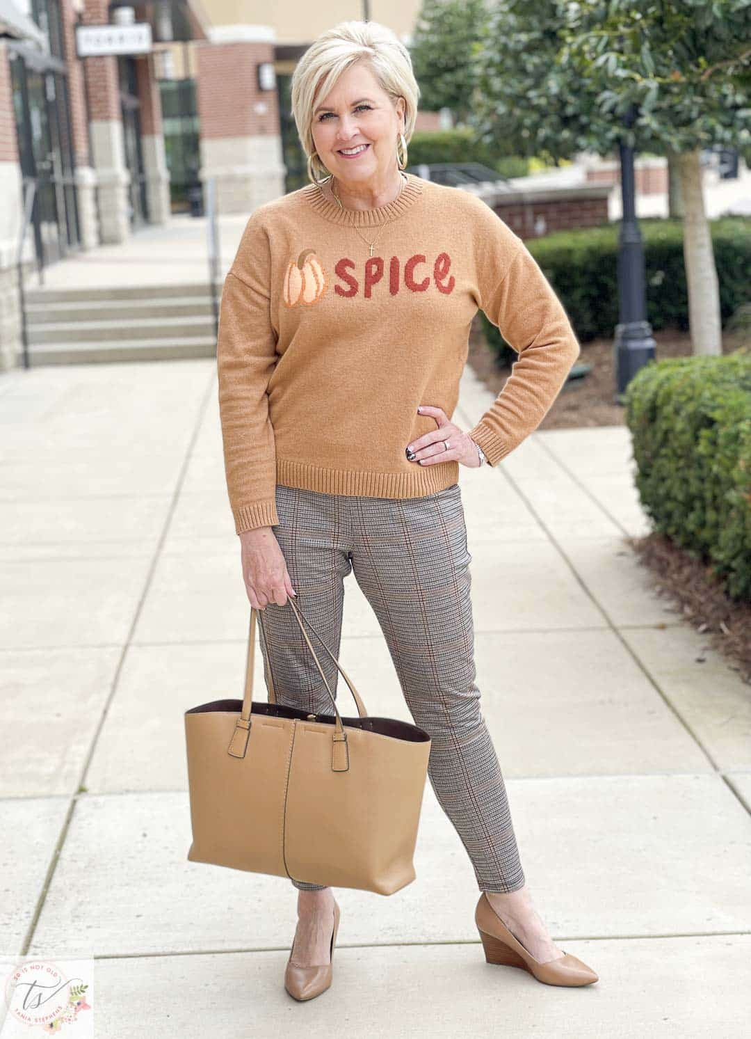 Over 40 Fashion Blogger, Tania Stephens, is wearing a Pumpkin Spice sweater with a pair plaid Ponte knit pants and taupe wedges
