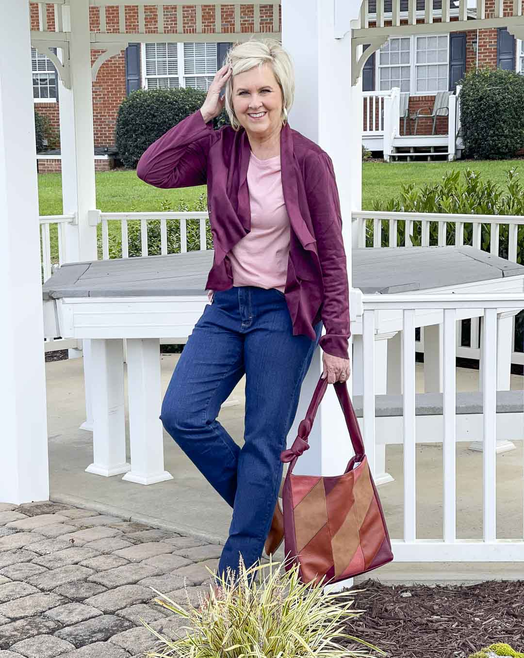 Over 40 Fashion Blogger, Tania Stephens, is showing her recent Walmart haul including this plum jacket, pink tee, bootcut jeans, and patchwork bag