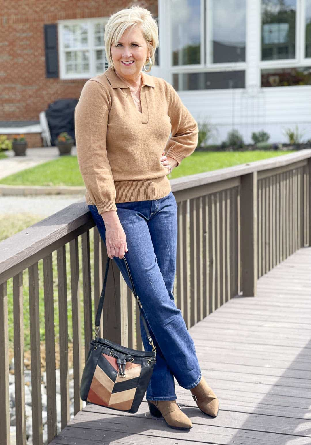 Over 40 Fashion Blogger, Tania Stephens, is showing her recent Walmart haul including this camel polo sweater, bootcut jeans, and patchwork bag