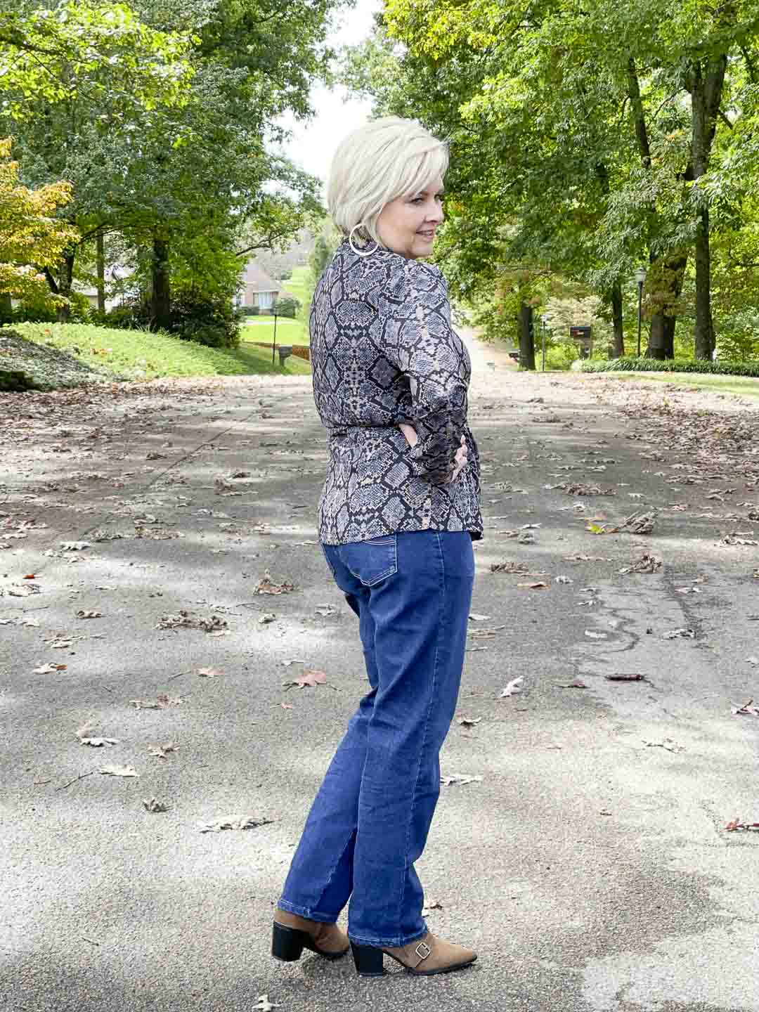 Over 40 Fashion Blogger, Tania Stephens, is showing her recent Walmart haul including this snake print wrap top, bootcut jeans, and ankle boots