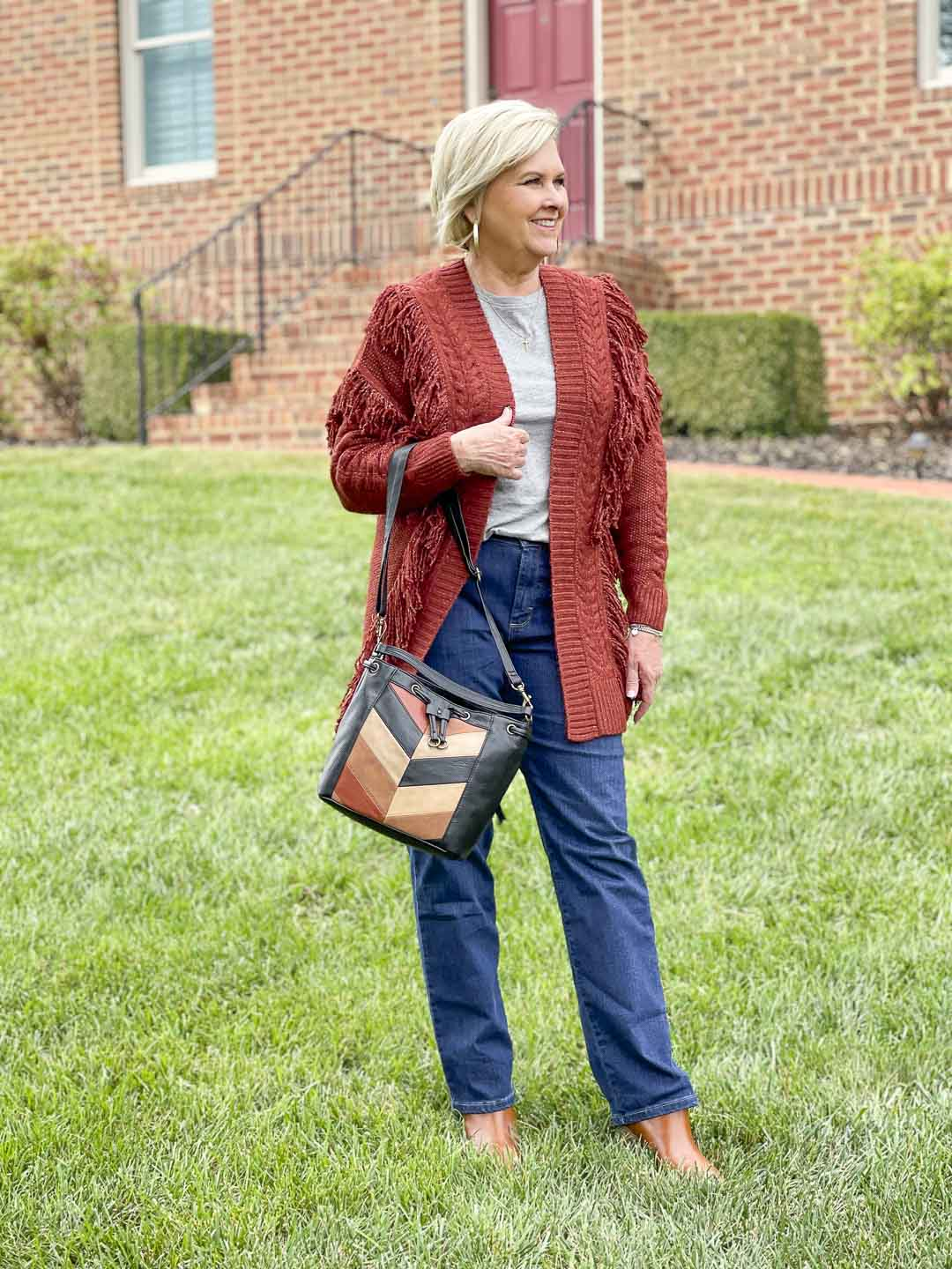 Over 40 Fashion Blogger, Tania Stephens, is showing her recent Walmart haul including this oversized fringed cardigan, bootcut jeans, patchwork bucket bag, and faux leather ankle boots