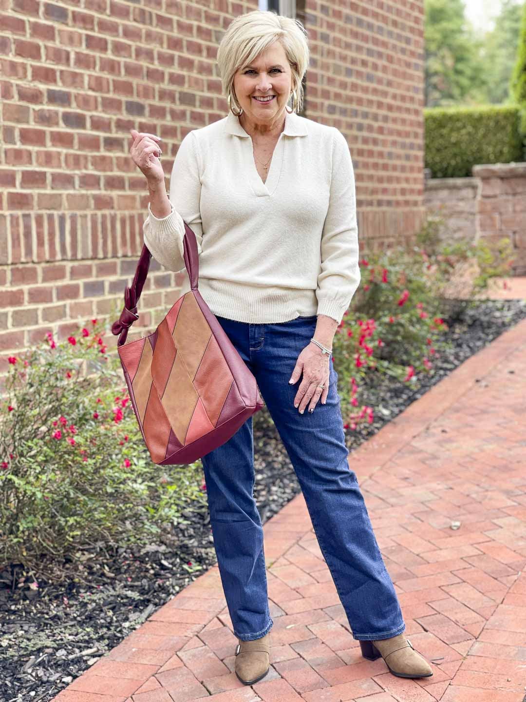 Over 40 Fashion Blogger, Tania Stephens, is showing her recent Walmart haul including this ivory polo sweater, bootcut jeans, and patchwork bag