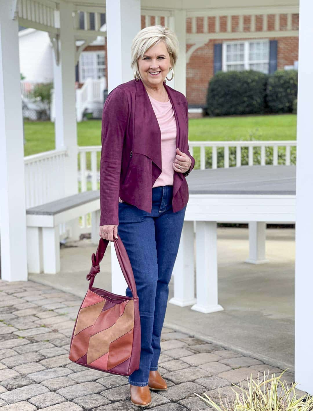Over 40 Fashion Blogger, Tania Stephens, is showing her recent Walmart haul including this plum moto jacket, pink tee, bootcut jeans, and patchwork bag