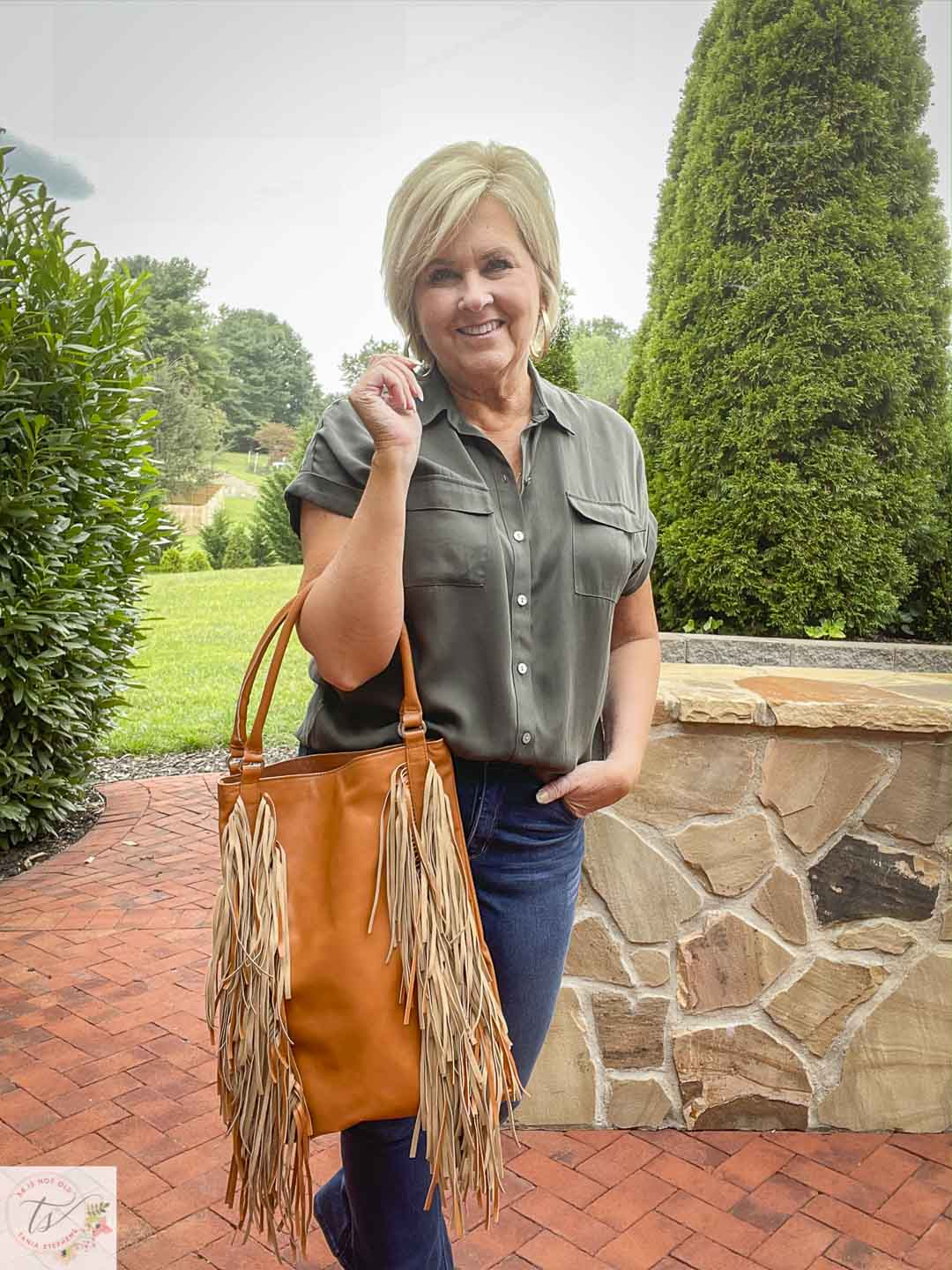 Over 40 Fashion Blogger, Tania Stephens, is wearing an olive button-up shirt and carrying a fringed handbag