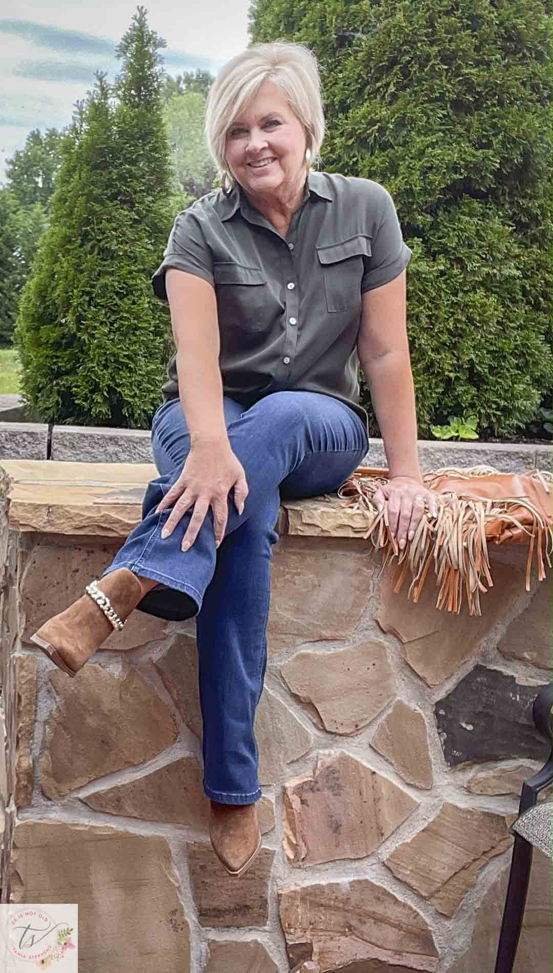 Over 40 Fashion Blogger, Tania Stephens, is wearing an olive button-up shirt, bootcut jeans, and suede ankle boots with a chain detail