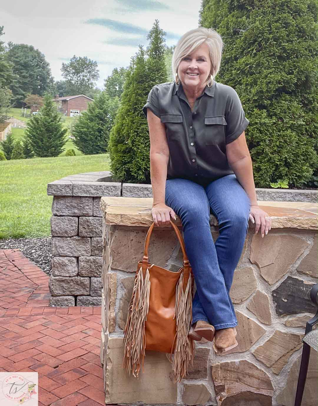 Over 40 Fashion Blogger, Tania Stephens, is sitting on a wall wearing an olive button-up shirt, bootcut jeans, and suede ankle boots