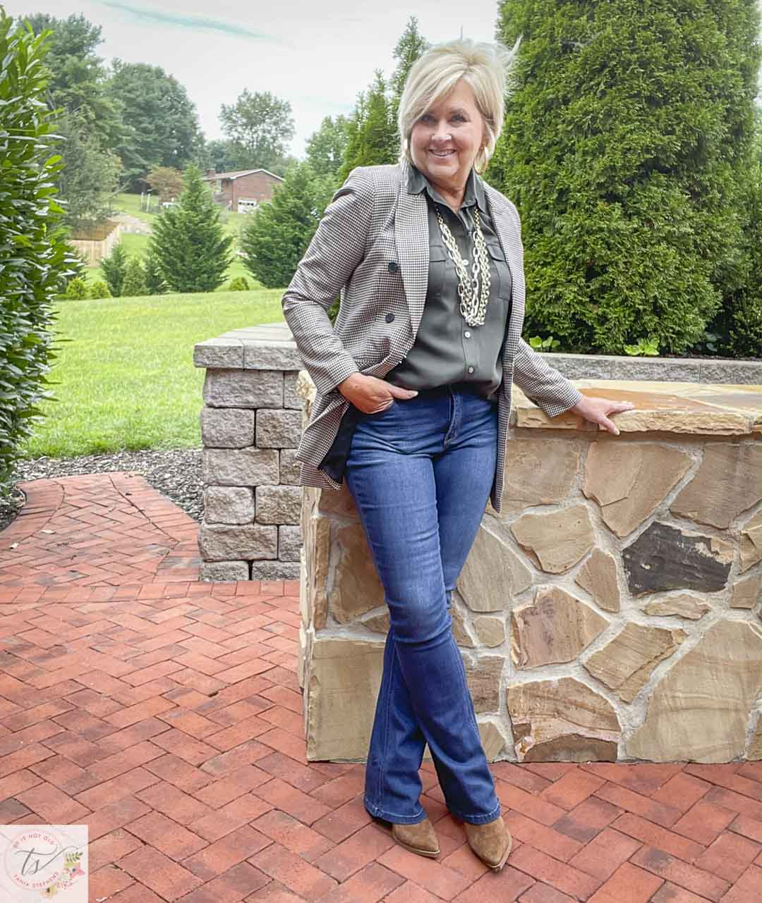 Over 40 Fashion Blogger, Tania Stephens, is wearing a plaid blazer with an olive button-up shirt, bootcut jeans, and suede ankle boots
