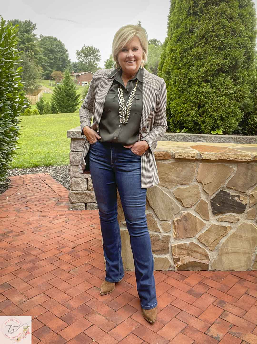 Over 40 Fashion Blogger, Tania Stephens, is wearing a plaid blazer with an olive button-up shirt, slim bootcut jeans, and suede ankle boots