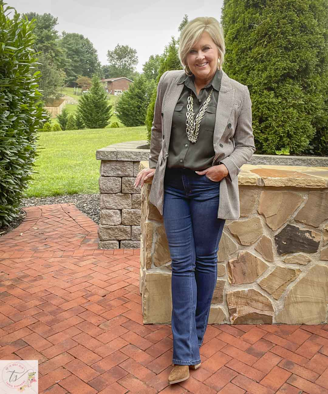 Over 40 Fashion Blogger, Tania Stephens, is leaning against a wall wearing a plaid blazer with an olive button-up shirt, bootcut jeans, and suede ankle boots