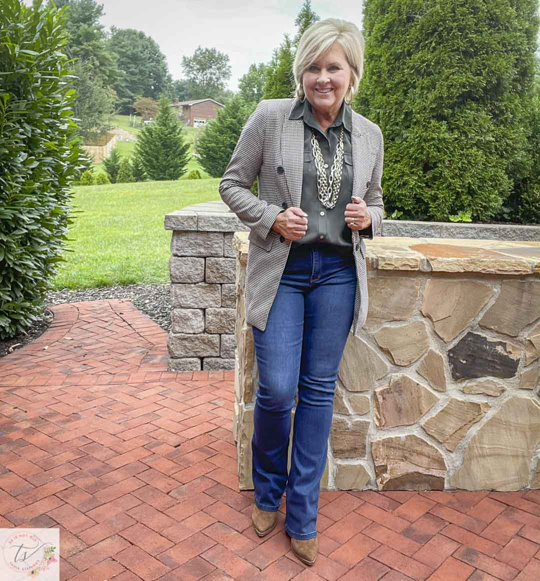 Over 40 Fashion Blogger, Tania Stephens, is wearing a plaid blazer with an olive button-up shirt, bootcut jeans, gold jewelry, and suede ankle boots
