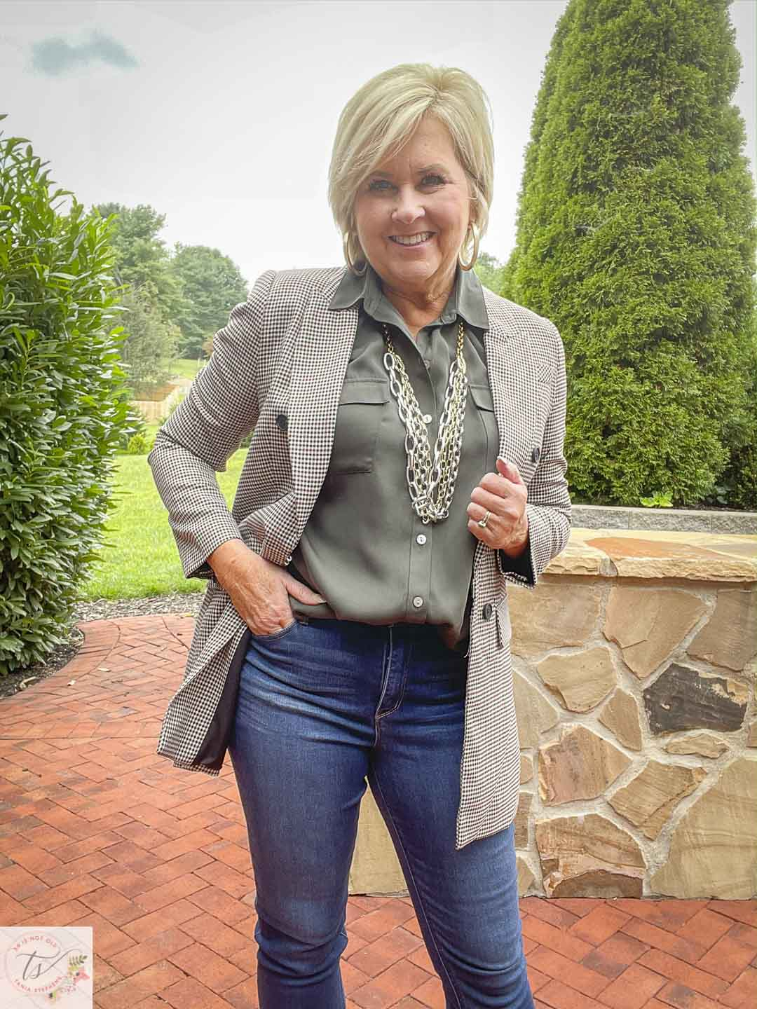 Over 40 Fashion Blogger, Tania Stephens, is wearing a plaid double breasted blazer with an olive button-up shirt