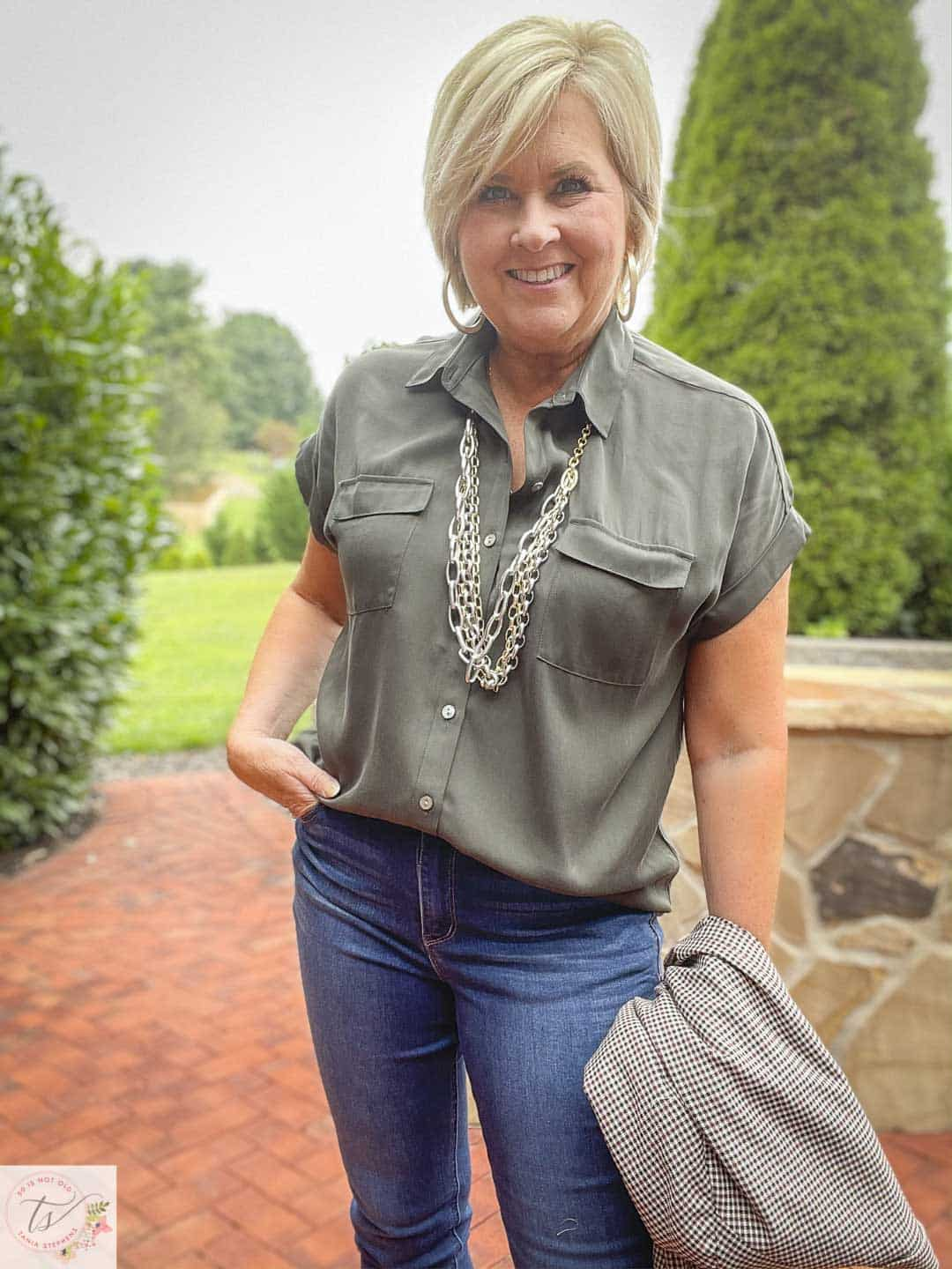 Over 40 Fashion Blogger, Tania Stephens, is wearing an olive button-up shirt, bootcut jeans, and gold jewelry